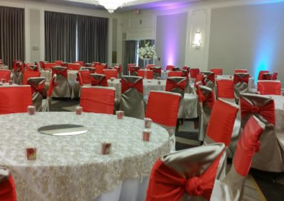 Silver satin chair covers with cherry red sashes