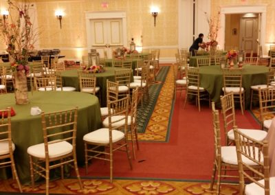 Gold chiavari chairs with forrest green polyester tablecloth
