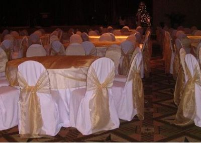 White poly chair covers w/ antique gold organza chair ties and overlay